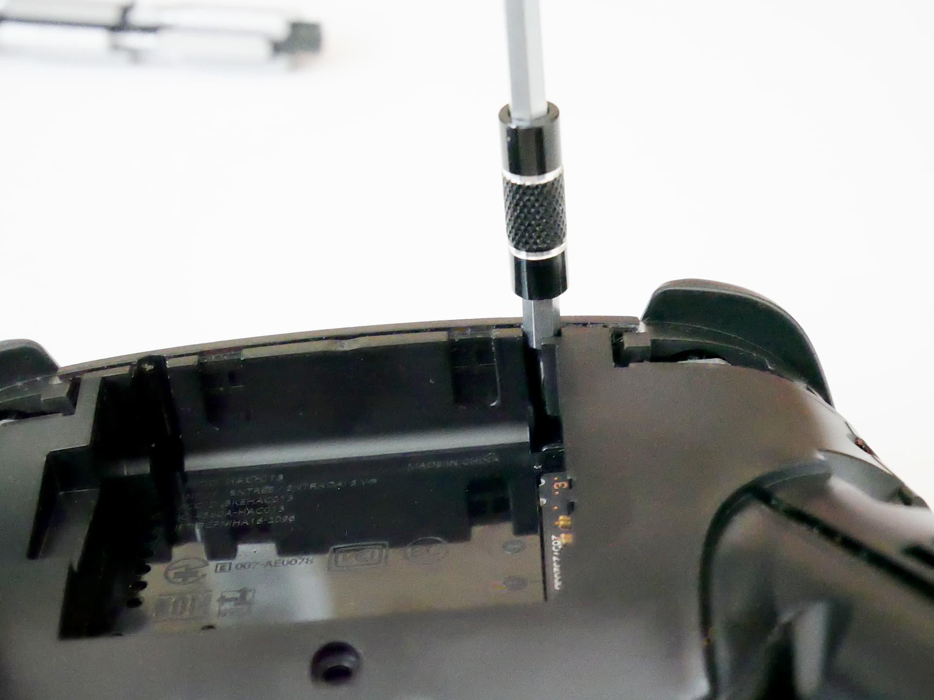 Nintendo Switch のプロコンをペン型電動ドライバーで分解している様子の写真