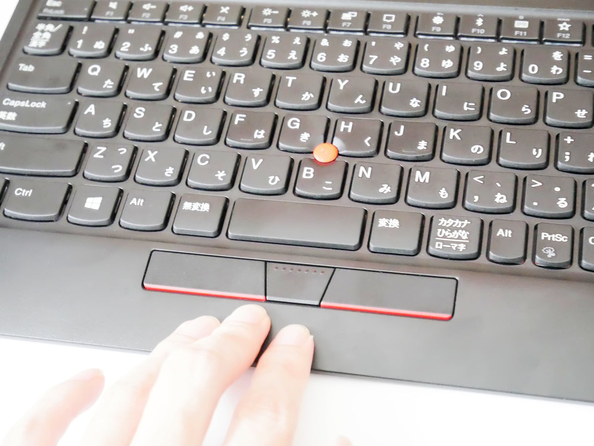 キーボードの中央部分を手で押している様子