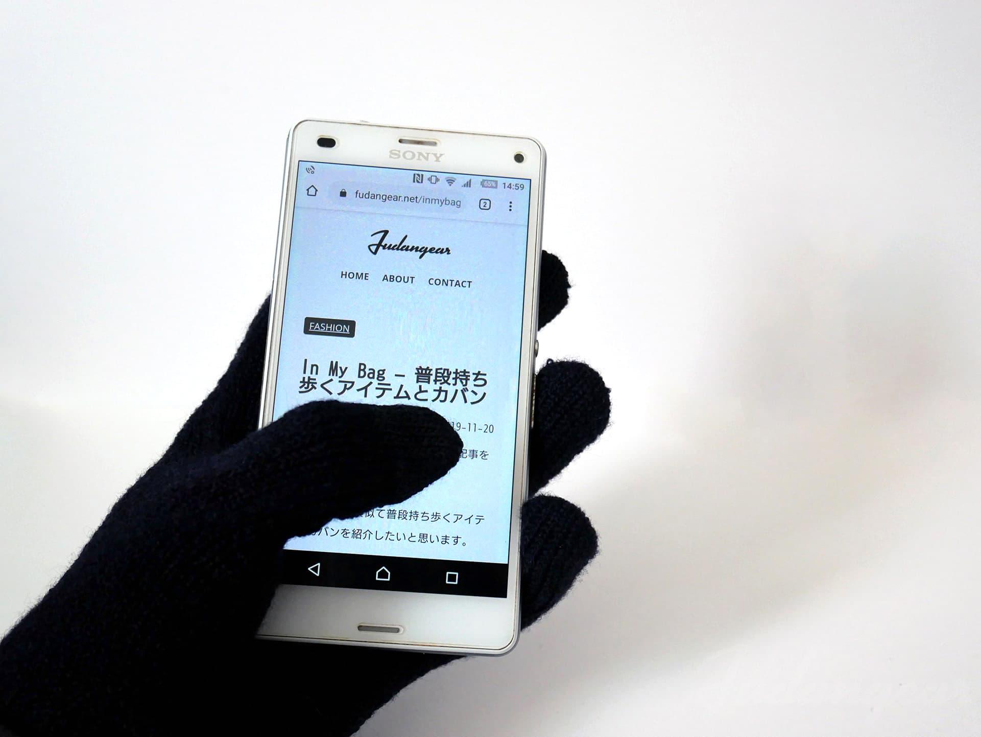 ウール混裏起毛タッチパネル手袋でスマホ画面を操作している写真